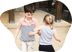 two kids dancing arm in arm