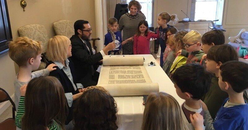 scribe restoring holocaust scroll with children around him