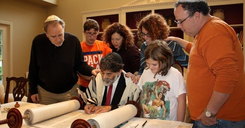 scribe restoring holocaust scroll with a family