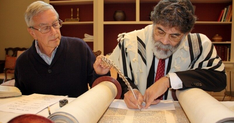 scribe restoring holocaust scroll with a man seated beside him