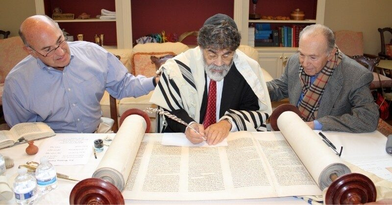 scribe restoring holocaust scroll with two men seated beside him