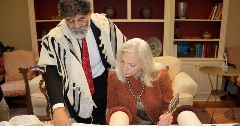 scribe helping woman with restoring holocaust scroll